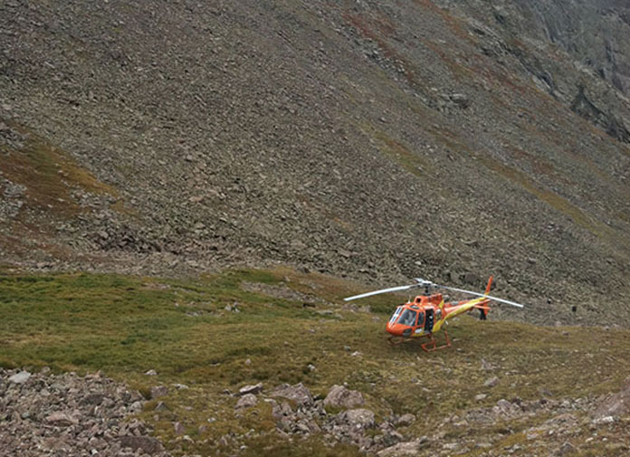 McFarland lands a helicopter on rough terrain.