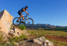 Mountain Biker jumps off a rock at Red Rock Canyon.