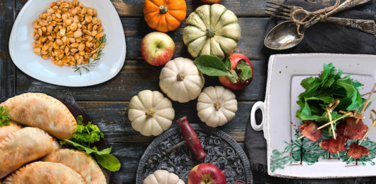 Autumn holiday recipes dishes set with decorative pumpkins, apples, red leaves with vintage cutlery, red wine, candle over wooden table. Rustic style.