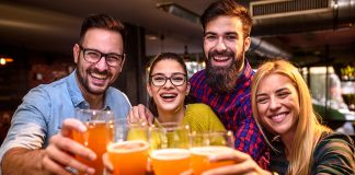 four people toast beers at trivia night