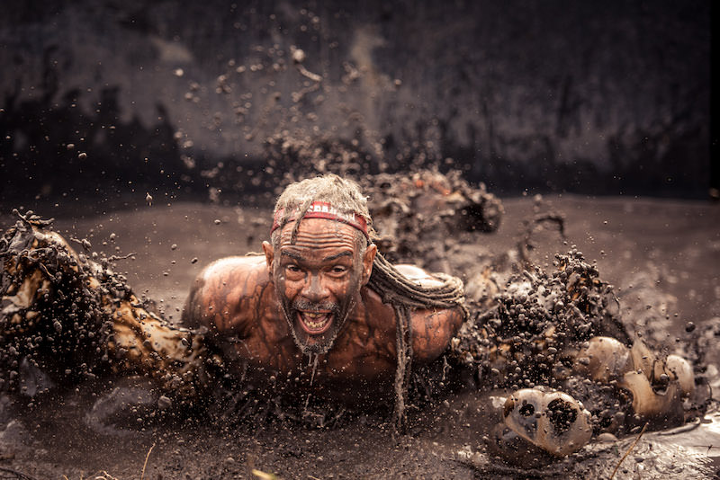 Runner crawling through the mud pit in an obstacle race.