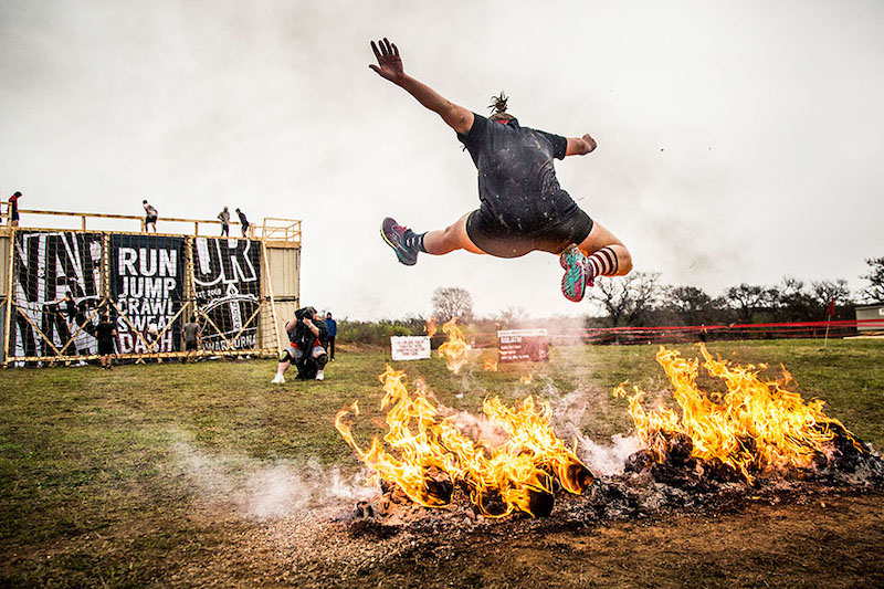 Runner jumping over fire in an obstacle race course.