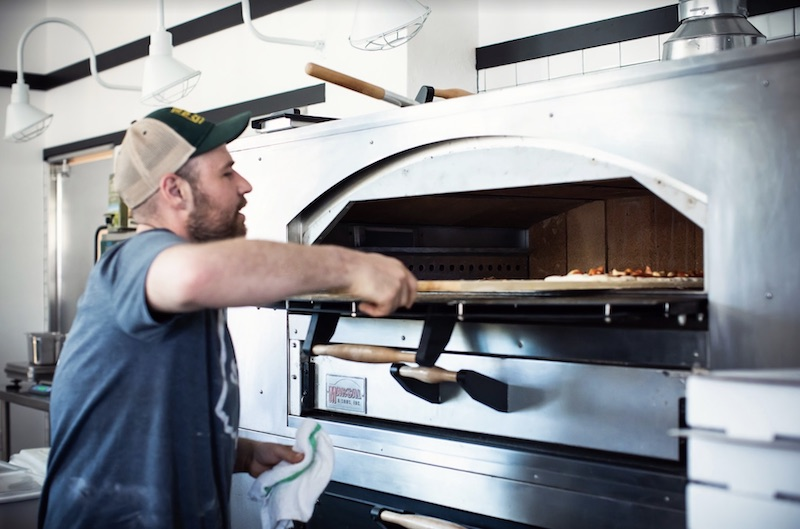 Pizza comes out of the oven at Stellina Pizza.