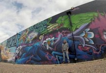Muji Rieger, director of the Knob Hill Urban Arts District, stands in front of one of the area's large-scale murals