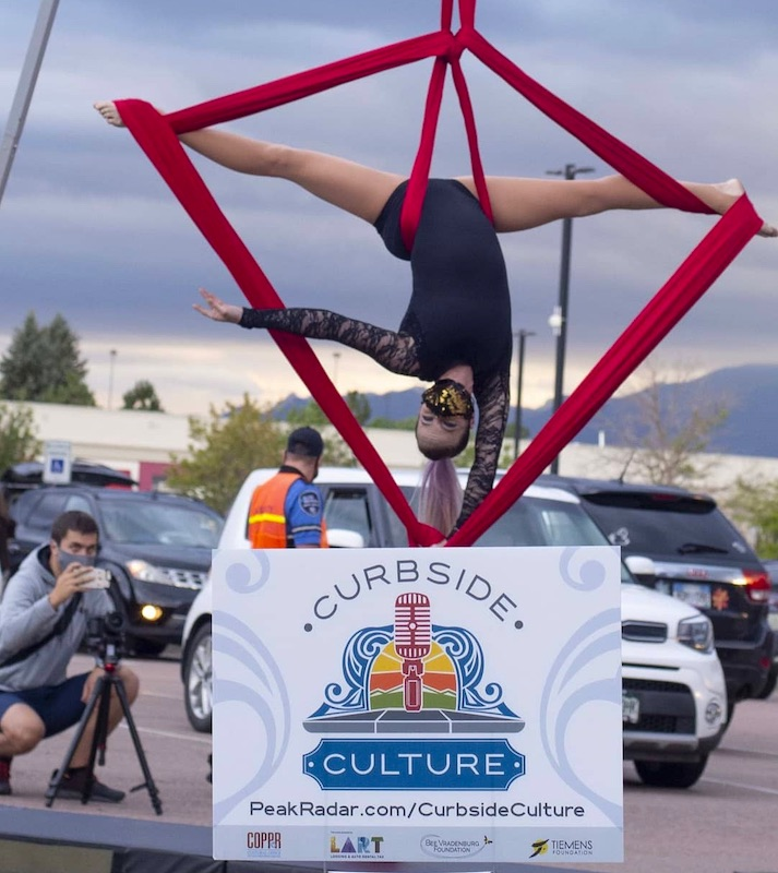 Dragonfly Aerial Company Curbside Culture performace. Girl gymanst performing with red fabric