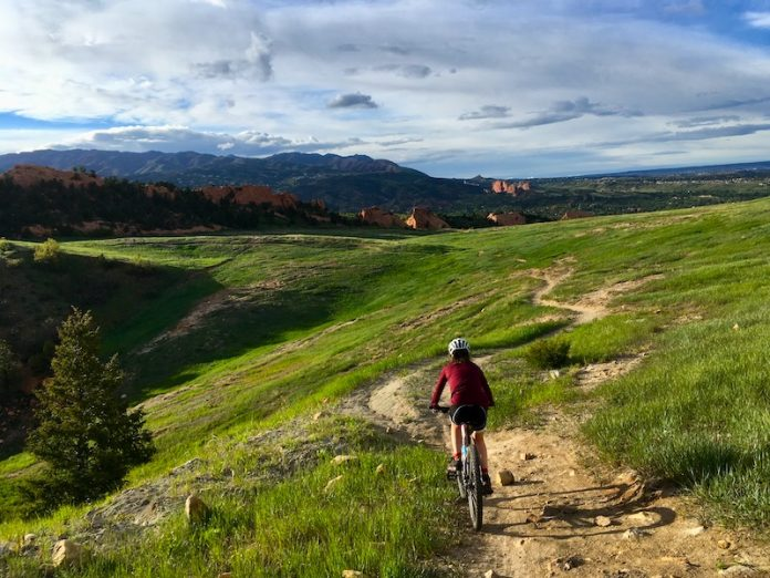 Biker rides easy mountain bikes trail in Red Rocks Canyon Open Space, Colorado Springs