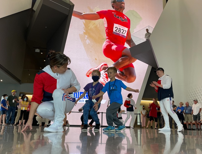 Kids run with athletes inside the US Olympic & Paralympic Museum